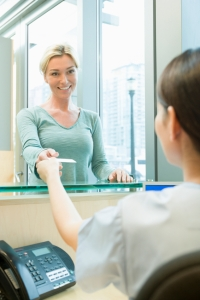 Female patient taking appointment card from receptionist at dentist's office